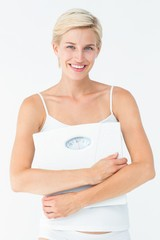 Smiling woman holding scales looking at camera