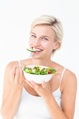 Beautiful blonde woman eating salad