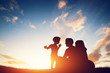 canvas print picture - Happy family together, parents with their child at sunset.