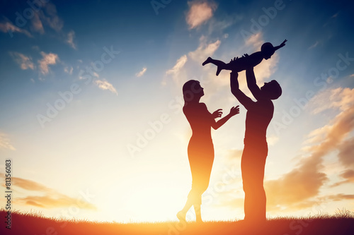 Happy family together, parents with their little baby at sunset