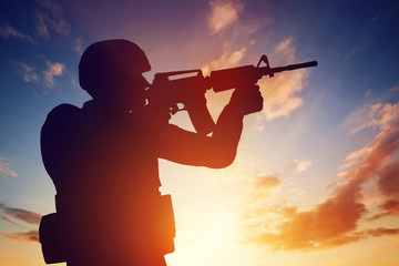 Soldier shooting with his rifle at sunset. War, army, military.