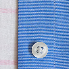 Strap shirt with a button close-up on white cotton fabric
