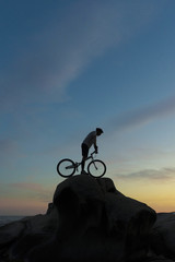 bmx rider action against sunset on the beach