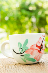 coffee cup on wooden board with blur background