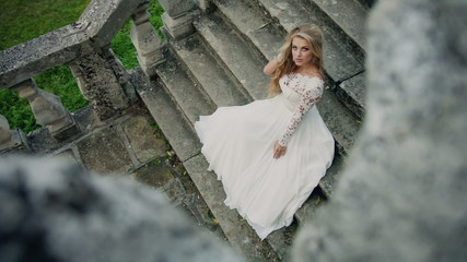 DOLLY MOTION: Beautiful modern bride sitting alone on the stairs