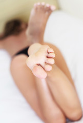 Clear feet of a woman lying in bed close up. Health care
