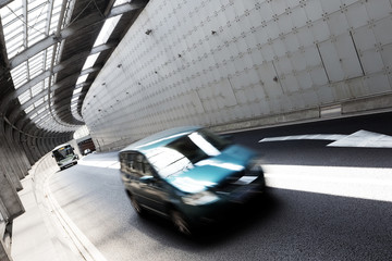 Car driving in tunnel of modern city