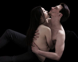 Bare-chested lovers couple on black background