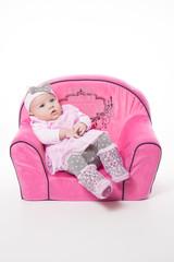 Kleine Prinzessin im rosa Kleid auf einem Sofa