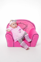Mädchen mit rosa Kleid auf einem Sofa