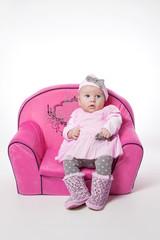 Süßes Baby im rosa Kleid auf einer rosa Couch