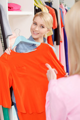 Woman chooses dress in a store