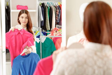 Woman chooses blouse in a store