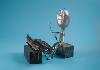 Recycled sculpture of a writer typing.
