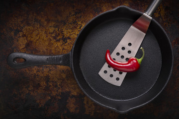 Red Chili Pepper and Spatula in a Cast Iron Pan