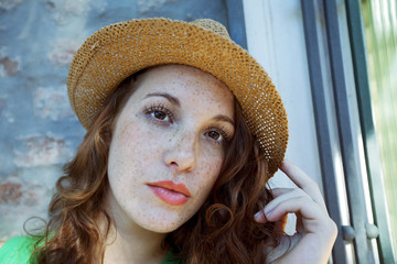 Young beautiful red haired woman wearing a hat