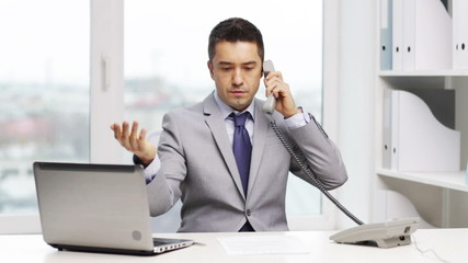 businessman with laptop calling on phone