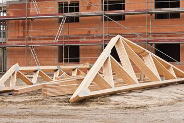 Fertigelemente aus Holz für einen Dachstuhl vor einem Rohbau