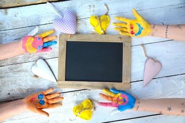 bunte Kinderhände mit Tafel