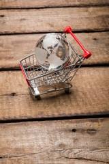 Market. Glass globe in the shopping trolley global market
