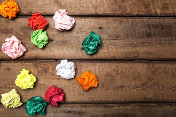 Background. Crumpled colorful paper on wooden background