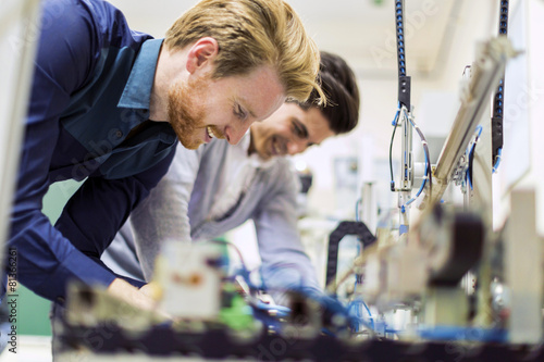 Two young handsome engineers working on electronics components - 81366261