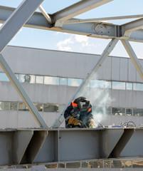 welder welds the steel bridge construction