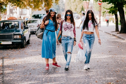 Three young girls walking on the street - 81366892