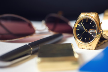 Men's accessory,pen, golden watch and lighter. Selective focus.