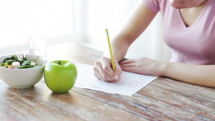 close up of young woman writing diet plan at home