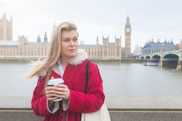 Beautiful blonde young woman holding cup of tea in London