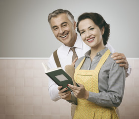 Wife and husband reading a cookbook together