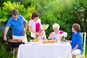 Big happy family enjoying bbq grill in the garden