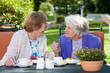 Happy Elderly Women Chatting at the Garden Table.