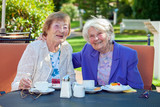 Happy Senior Women Relaxing at the Garden Table.