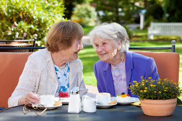 Two Senior Women Relaxing at the Outdoor Table.
