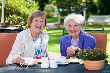 Two Happy Senior Ladies Having Snacks Outside.