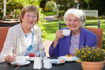 Senior Women Having Coffee at the Garden Table.