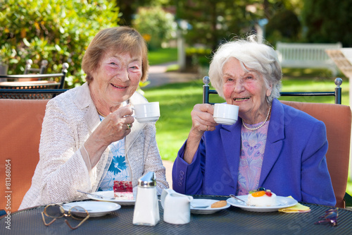 Leinwandbild Motiv Elderly Best Friends with Coffee at Outdoor Table.