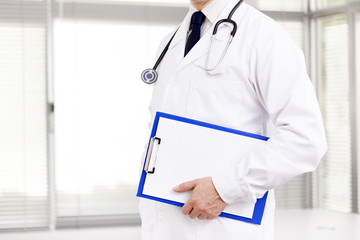 Doctor holding a blue clipboard at the clinic