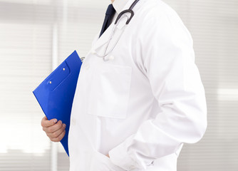 Doctor holding a blue clipboard at his office