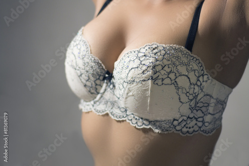 Foto op Aluminium Akt Woman wearing a white brassiere isolated on a gray background