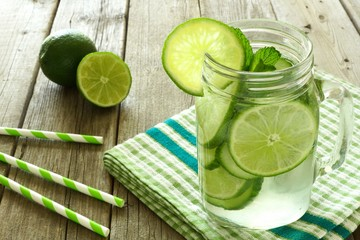 Detox water with lime and cucumbers in mason jar on wood table
