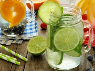 Various types of detox water with fruit in mason jars on wood