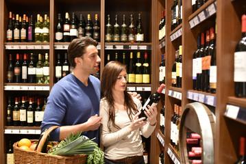 junges Paar kauft Flasche Rotwein im Supermarkt ein