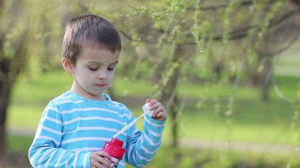 Two adorable little boys, playing with soap bubbles in the park