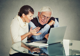 woman teaching confused elderly man how to use laptop