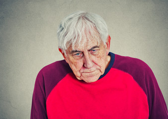 Portrait of an elderly depressed man on gray wall background
