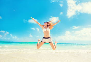 Happy Woman Jumping In The Air having fun On Tropical Beach