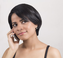 Young latin woman smiling using phone